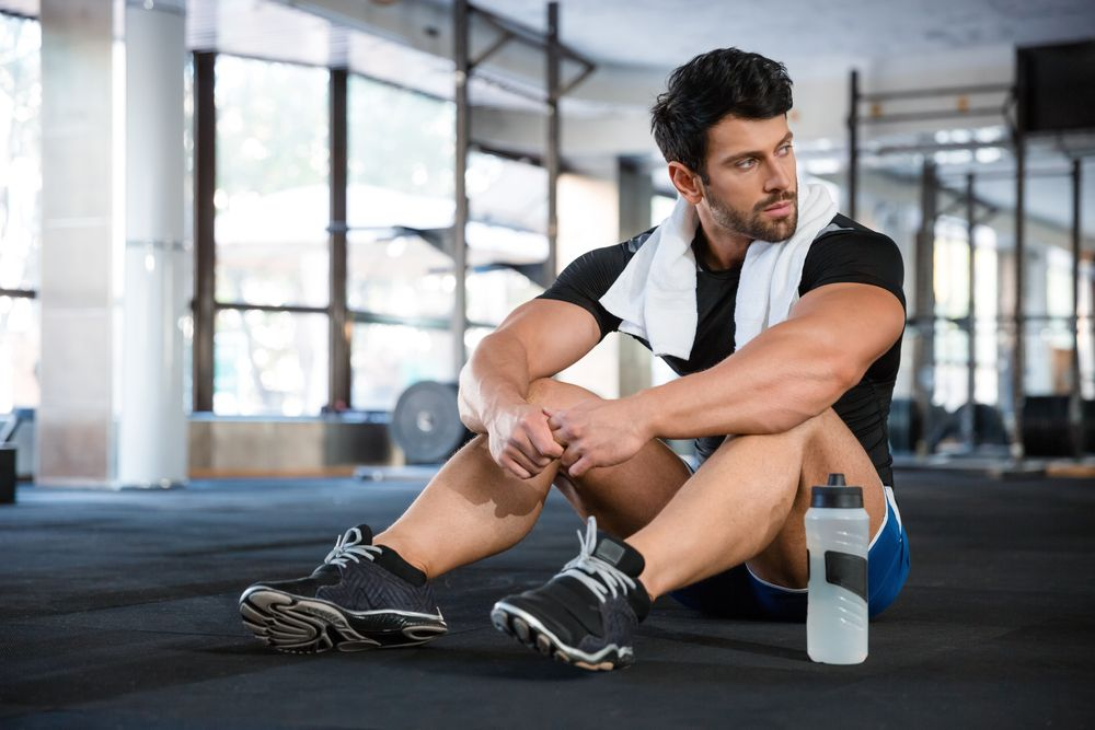 fit man sitting in gym with towel around neck