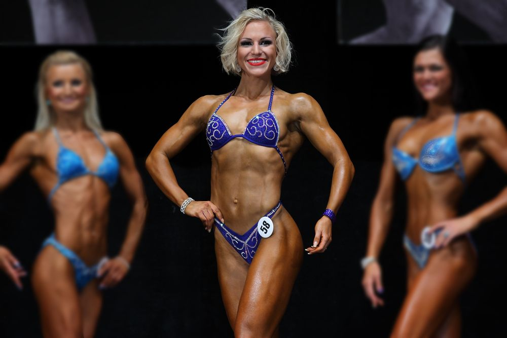 fitness woman competing on stage with two fitness women in the background