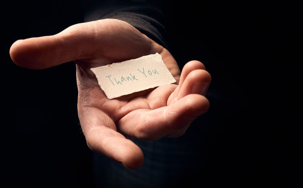 hand holding a card that says thanks on black background
