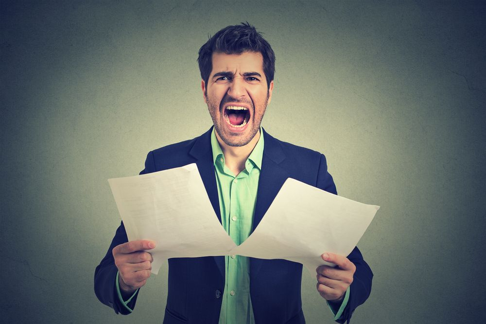 businessman shouting while holding papers