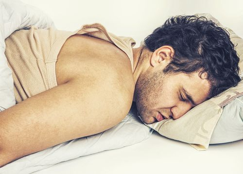 sick man lying in bed face down