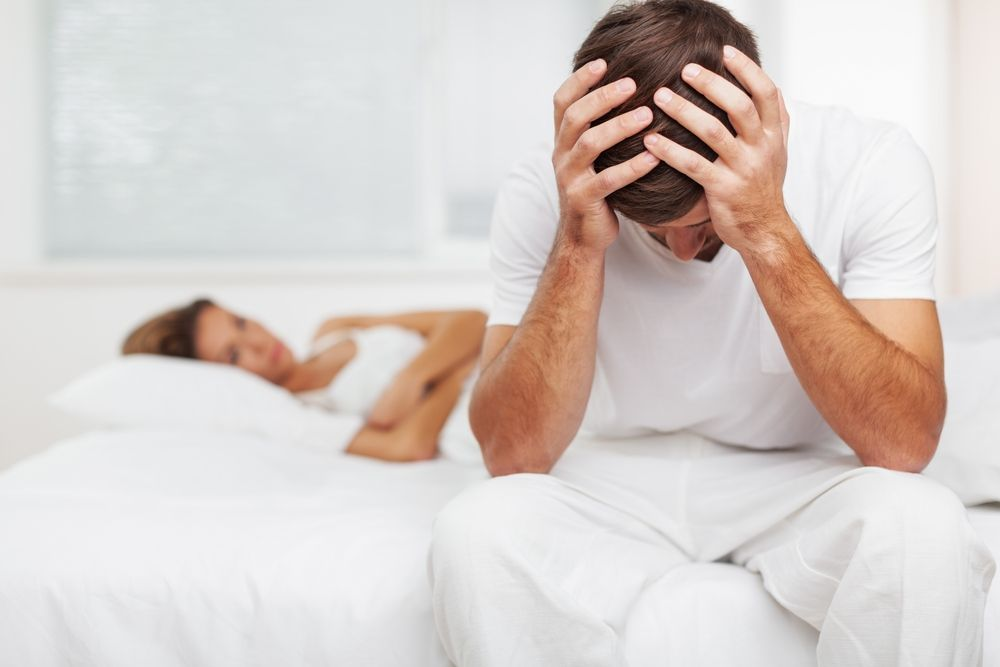 man holding head in bed with woman