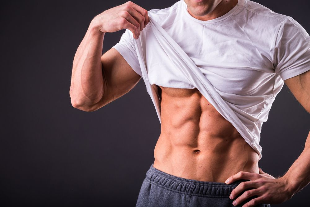 muscular man lifting white shirt to show abs