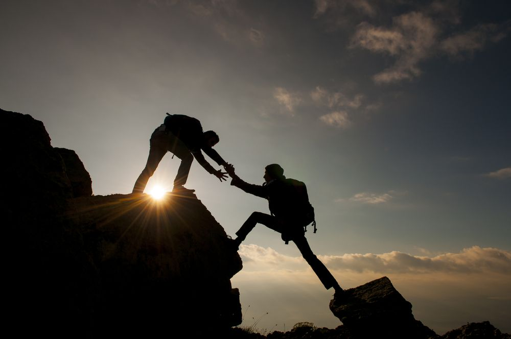 one person helping another person climb mountain in dark