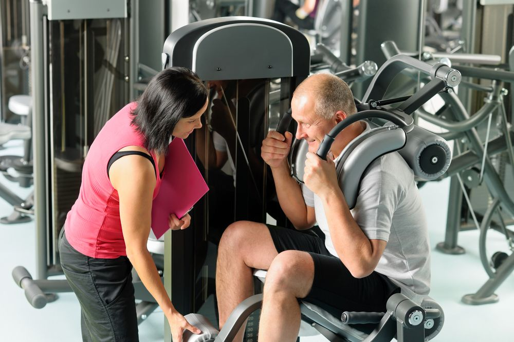 woman personal trainer with client in machine