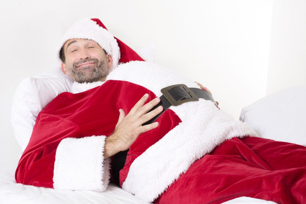 santa lying in bed smiling with hand on belly