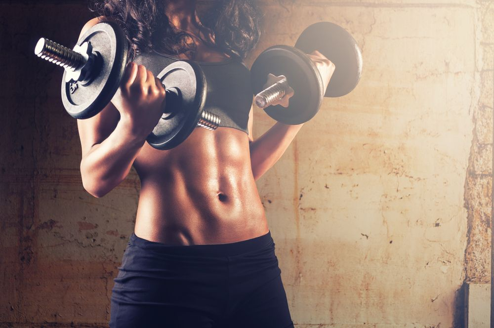 Woman with muscular body lifting weights