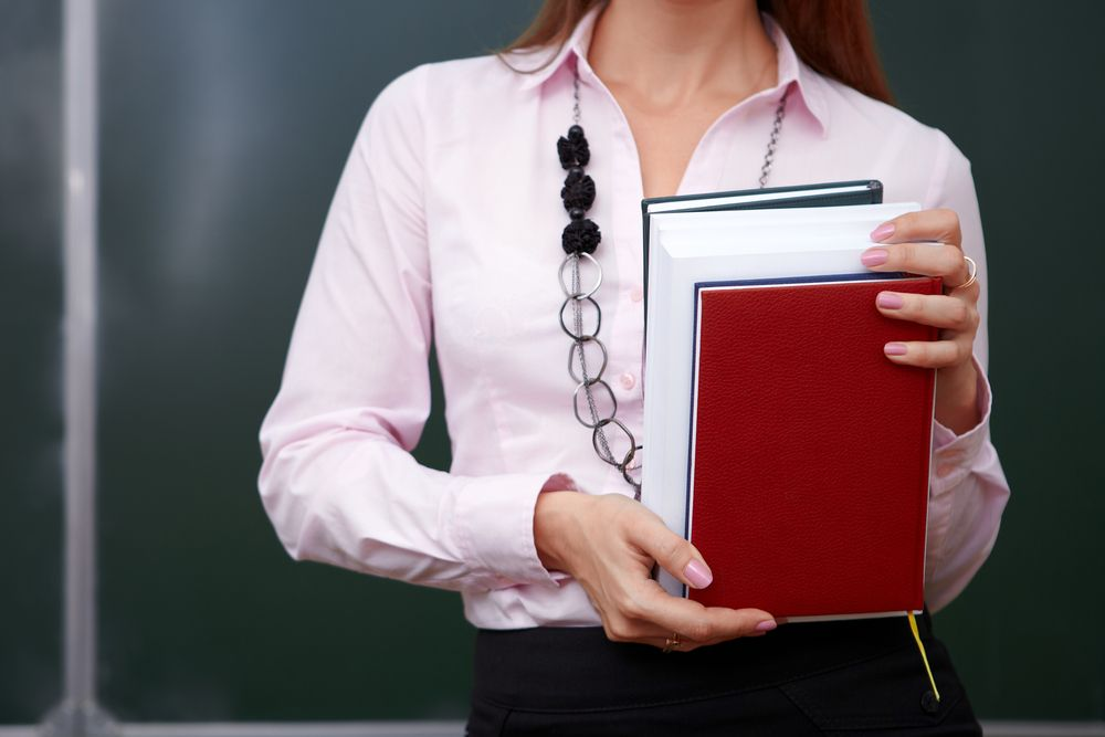 woman in front on blackboard holding books