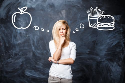 woman standing in front of chalkboard deciding