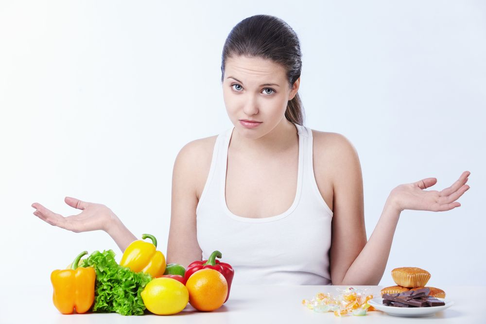woman deciding between fruits and vegetables and junk food