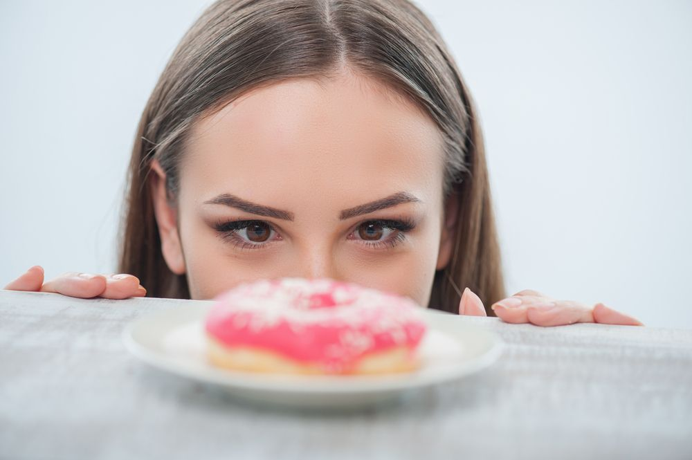 woman looking at a donut on the table