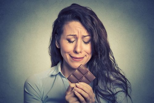 woman staring unhappily at chocolate