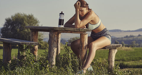 Female athlete resting with sports water bottle