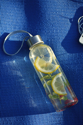 Glass water bottle filled with water and fruit