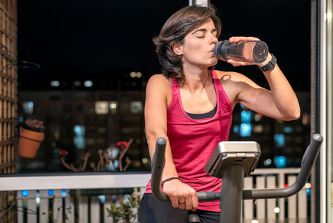 Healthy woman exercising holding plastic sports water bottle