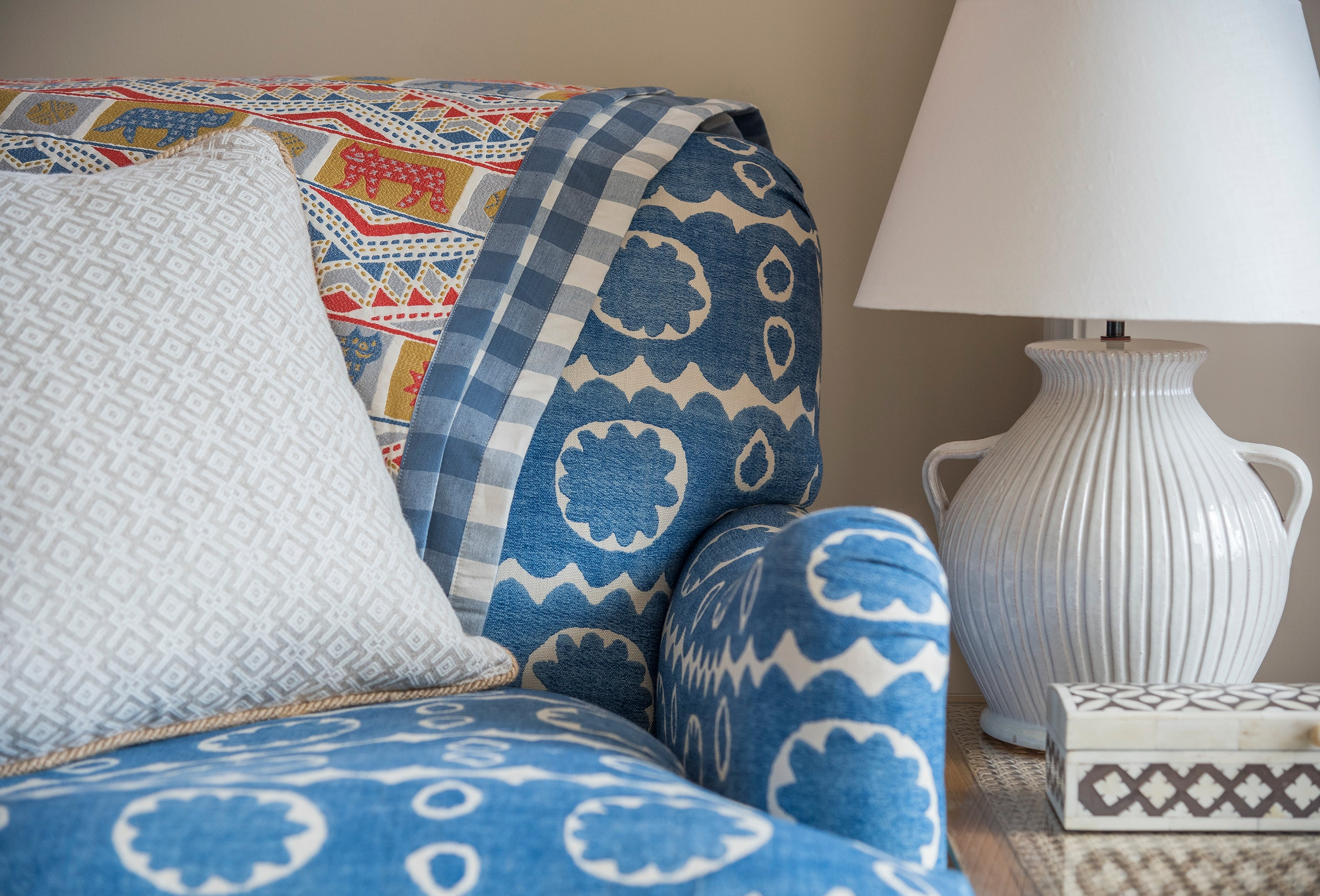Our reversible tiger tiger throw features a whimsical , guatemalan-inspired design with a blue and white gingham on the other side.