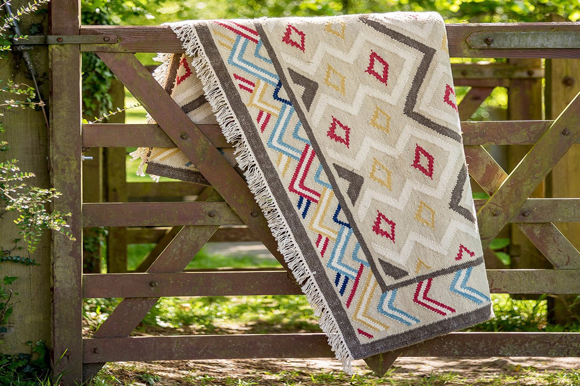 Wicklewood Osborne rug is a handwoven flatweave rug that mixes diamond motifs in the ground with a strong colourful zig zag.