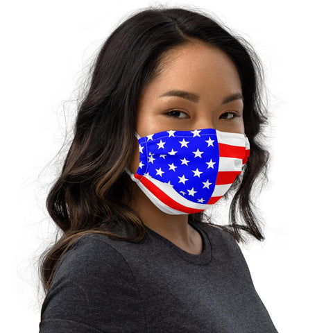 A woman with brown hair wearing a premium white face mask with the United States of America flag imprinted red white and blue