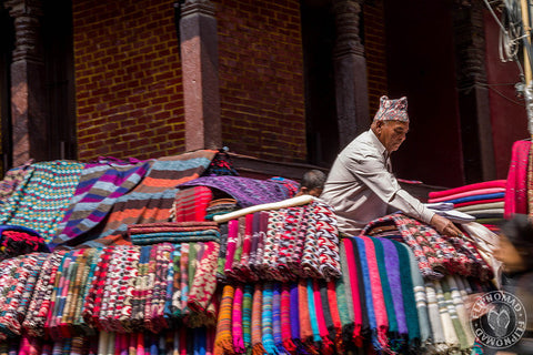 A seller is arranging Yak wool shawls for sale