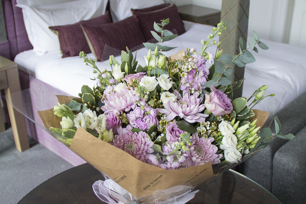 Beautiful corporate flower supply from Rose N Thyme for Blythswood Square Hotel Glasgow. The bouquet is on a table in front of a four poster bed