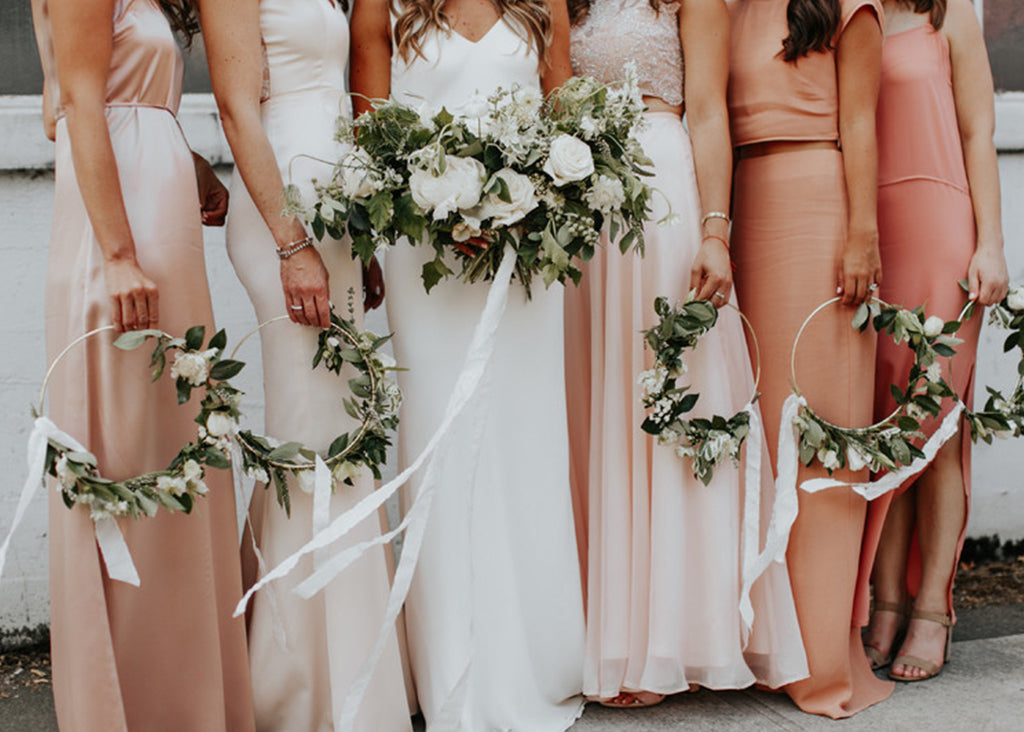 Bridesmaids holding floral wreaths