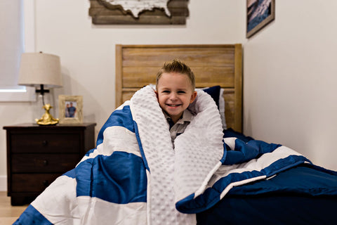 Little boy sitting on the end of a bed with a blue and white striped Beddy's blanket wrapped around his shoulder.