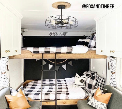 The image of the interior of an RV, showing a set of raw wood built-in bunks. Bunk are showing Beddy's black and white buffalo check Checked Out Beddy's. Two couches sit in front of the beds with faux leather accent pillows.