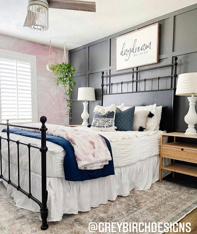 A dark wood work wall sits behind a queen bedframe that features our ruched Chic White Beddy's with navy and pink accents.