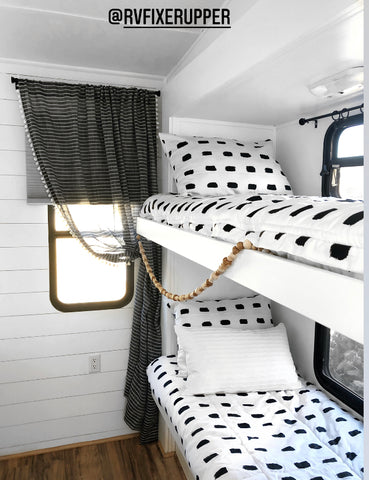 The inside view of a set of RV bunk beds on the wall to the right. Both beds feature Beddy's white with black dashes Dash Beddy's.
