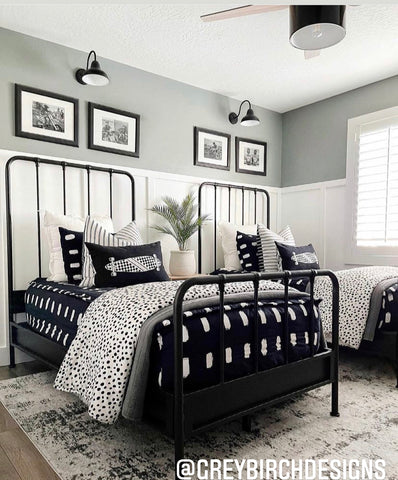 An image of a bedroom with white board and batten three-fourths of the way up the walls and a greenish/gray paint above that. Two twin beds feature our black with white dashes- Jet Beddy's and black and white accent items.