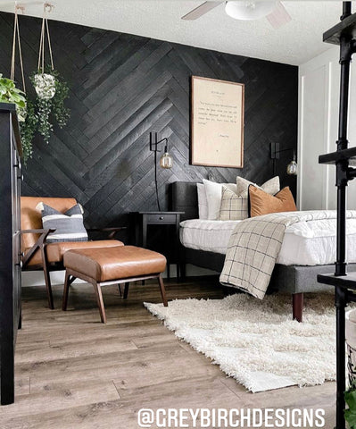 An image of a bedroom featuring a black herringbone wall with a twin bed in front. Bed features our Love at First White Beddy's and tan and black accents.