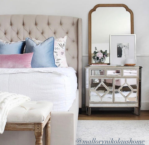 The front view of a master bedroom showing the right half of the bed with a glamour glass nightstand to the right and a old framed mirror hanging above. Bed features our Love at First White Beddy's and is accented in blue and mauve accented pillows, one including a floral design in the same colors.