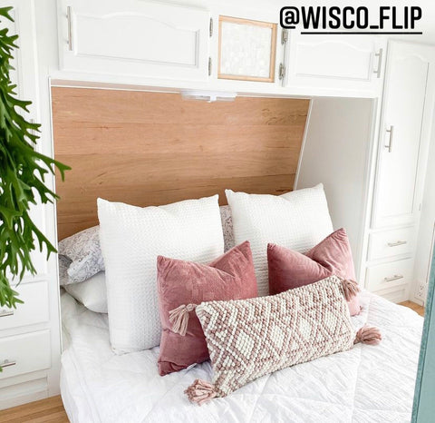 A close up image of an RV bed with a natural wood built-in headboard, white cabinets hanging above, Beddy's Love at First White Beddy's on the floor-style bed, with mauve pink accent pillows.