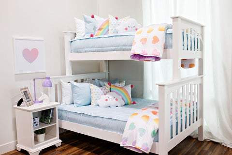 Light blue bedding on a white bunk bed with multi-color pastel rainbow heart blankets and pillows.