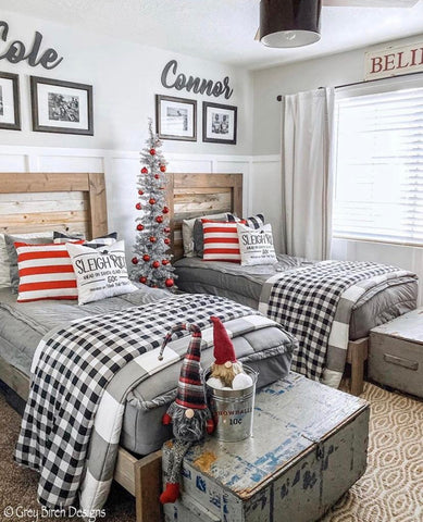 An image of a bedroom with white board and batten three-fourths of the way up the wall with a neutral paint above that. Two twin beds feature our Modern Gray Beddy's with red and white pillows and a Christmas tree in between the beds.