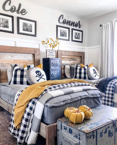 An image of a bedroom with white board and batten three-fourths of the way up the wall with a neutral paint above that. Two twin beds feature our Modern Gray Beddy's with mustard colored accents included a few stuffed pumpkins and throw blanket.