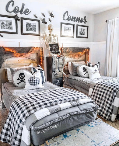 An image of a bedroom with white board and batten three-fourths of the way up the wall with a neutral paint above that. Two twin beds feature our Modern Gray Beddy's with orange lights on the bed and other halloween themed decor.