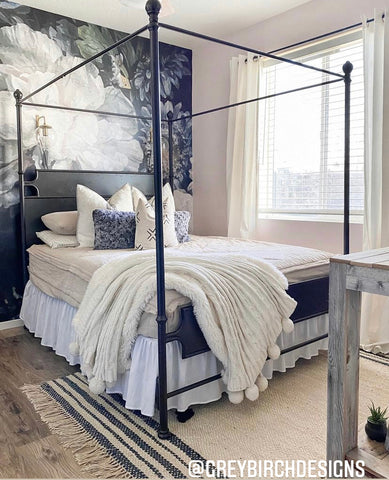 A dark black floral wallpaper sits behind a queen size bed that features our oatmeal colored Naturally Boho Beddy's.