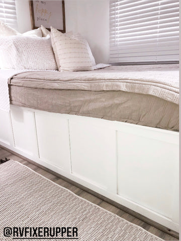 A close up image of the side of a white  RV bed with Beddy's oatmeal colored- Naturally Boho Beddy's on the bed.