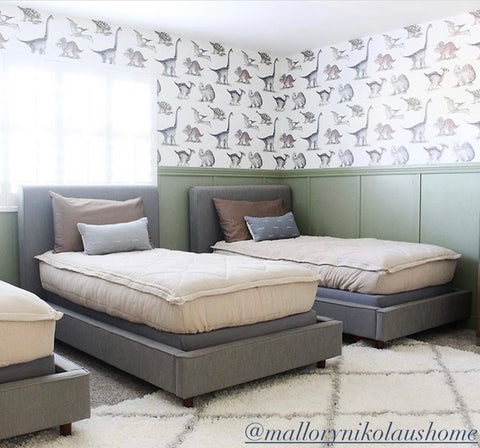 Three twin beds sit in a bedroom with board and batten half way up the surrounding walls painted olive green and a multi colored dinosaur print wallpaper goes up the remaining top half of the wall. Beds all feature our oatmeal colored Naturally Boho Beddy's.