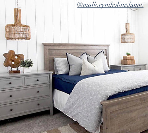 A dark brown queen bedframe sits in front of a white vertical striped shiplap wall. Gray nightstands sit to each side of the bed and wicker coastal style hanging light pendants hang above each one. Bed features our Nautical Navy Beddy's.