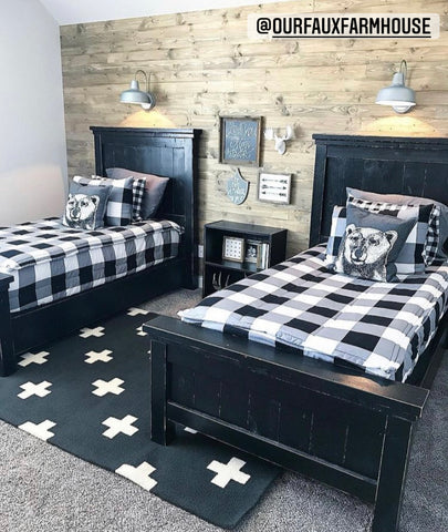A shared room with two black twin beds, both featuring our black and white Checked Out Beddy's. A rustic wood wall sits behind the beds and a black rug with white swiss cross sits in between the beds.