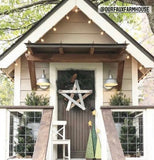 Image of a tan colored playhouse, with a porch overhang, white trim and brown door.