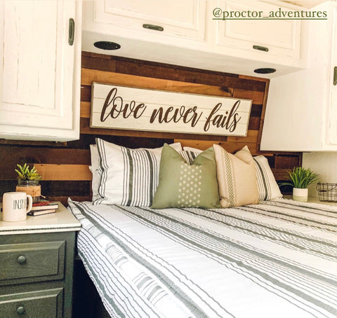 The inside view of an RV bed with a wood slat wall behind the bed and white cabinets hanging a few feet above the head of the bed. The bed features our Farmhouse Beddy's and sage green pillow covers.