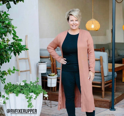 An image of a woman with short blonde hair standing in the doorway with her hand on her hip and some furniture seen behind her in the distance.