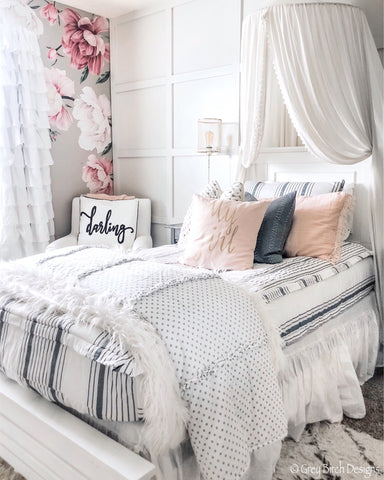 A white wall with white squares in wood trim work sits behind a white twin size bed. The adjoining wall is covered in tan wallpaper with large pink flowers and white ruffled curtains frame a window on the center of that wall. The bed features our Farmhouse Beddy's with pale pink accents.