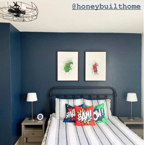 A dark gray/green wall sits behind a black bed frame featuring our Farmhouse Beddy's and Super Hero Accessory Bundle. Two watercolor superhero themed prints hang above the bed and an industrial style fan light lights up the room.