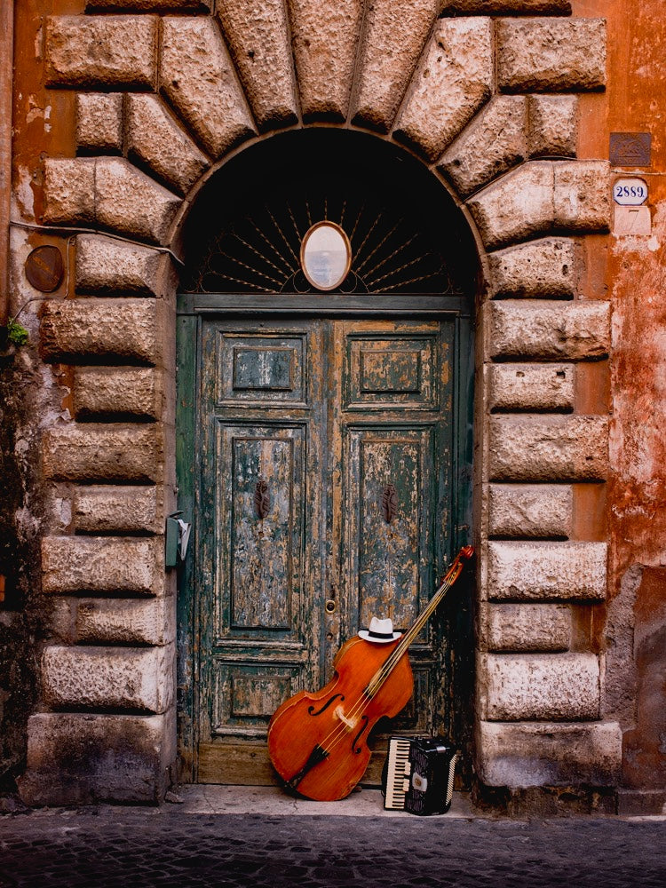 Photograph of a cello leaning in a brick archway in Italy