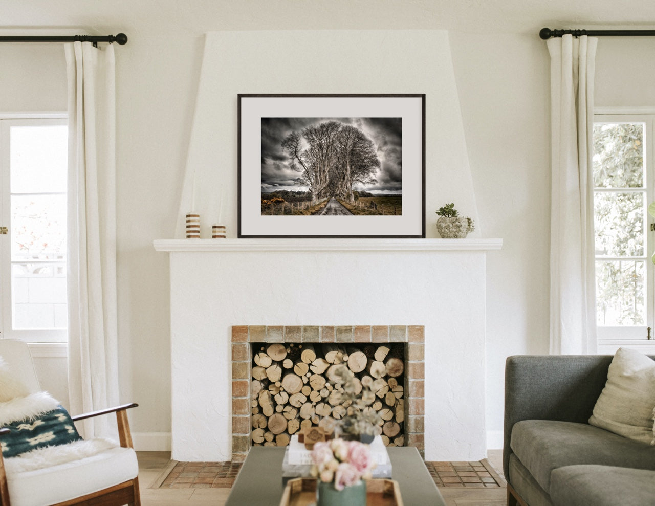 Fireplace mantel with framed black and white tree art