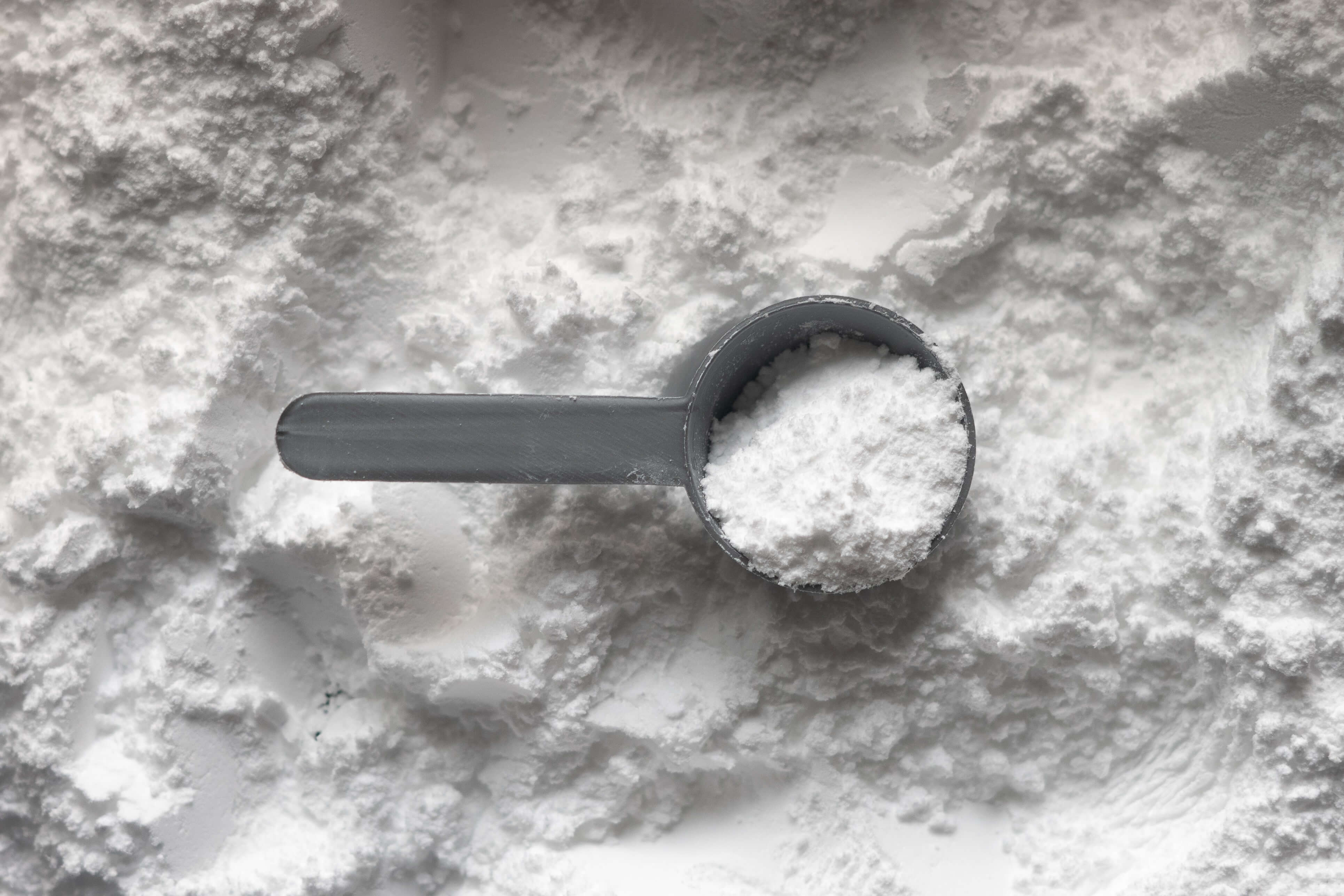A grey scoop containing white powder